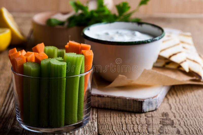 Carrot and celery sticks, yogurt dip with parsley  served  on rural table. Fresh vegetables carrot, celery sticks, yogurt dip with parsley and lemon juice served stock images