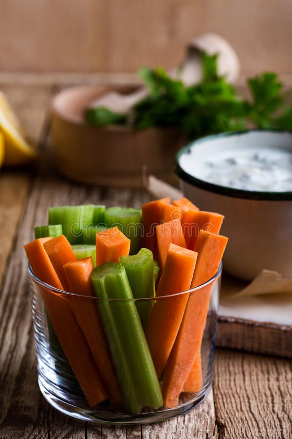 Carrot and celery sticks, yogurt dip with parsley  served  on rural table. Fresh vegetables carrot, celery sticks, yogurt dip with parsley and lemon juice served stock photos