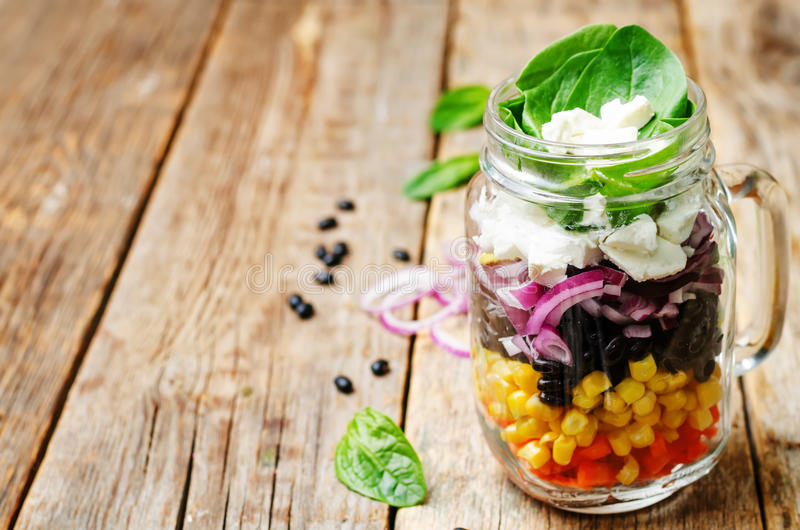 Carrot corn black beans red onion feta spinach salad. In a jar. toning. selective Focus royalty free stock image