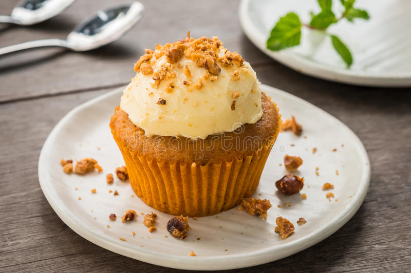 Carrot cupcake with cream cheese and hazelnuts stock image