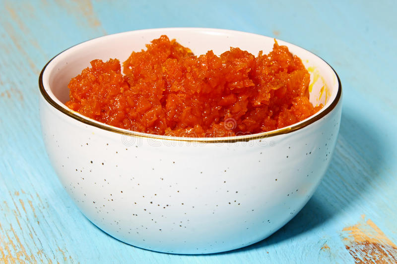 Carrot or Gajar halwa. Carrot halwa or Gajar halwa, an Indian dessert in a bowl on blue wooden background royalty free stock image