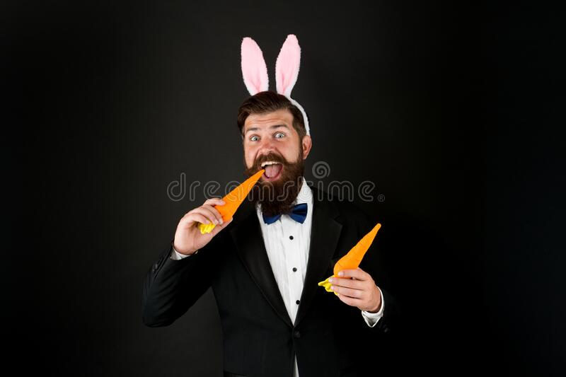 Carrot is good for your teeth. Celebration Easter holiday. Easter day. Event host. Celebrate Easter. Bearded man with royalty free stock photos
