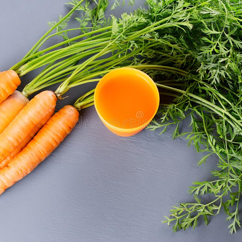 Carrot juice and carrots close up on a grey wooden background royalty free stock photo