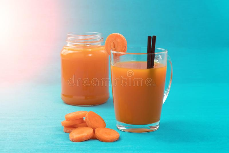 Carrot juice in a glass on a blue background, close-up. Concept of a healthy diet, diet royalty free stock photo
