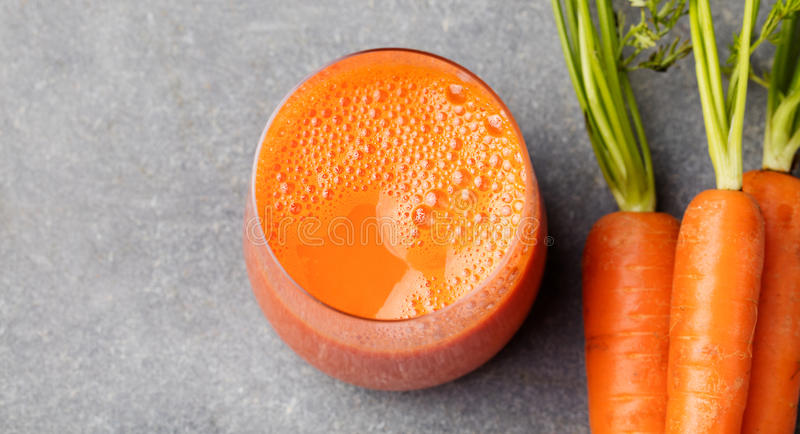 Carrot juice in glass and fresh carrots Healthy food on a grey stone background Top view royalty free stock images