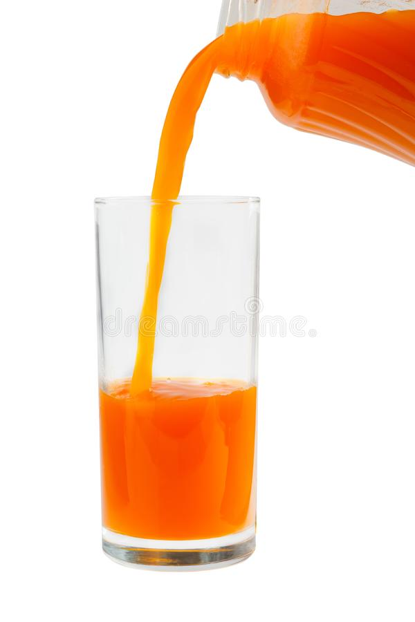 Carrot juice is poured into a glass from the bottle royalty free stock photography