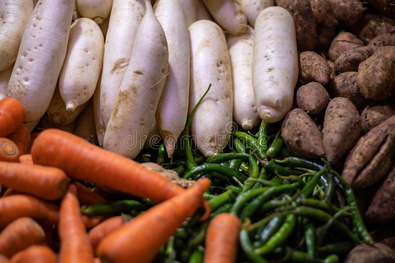 Carrot, radish, sweet potato and pepper piles on market stall. Organic farm market table with ripe vegetables. Healthy food cooking ingredient. Asian food royalty free stock photography