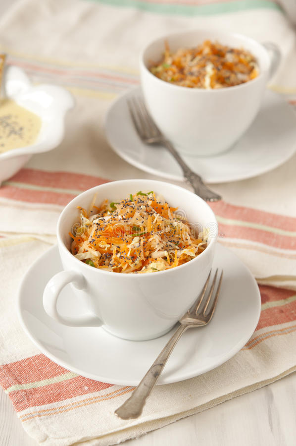Carrot salad. With poppy seeds in white bowls royalty free stock images