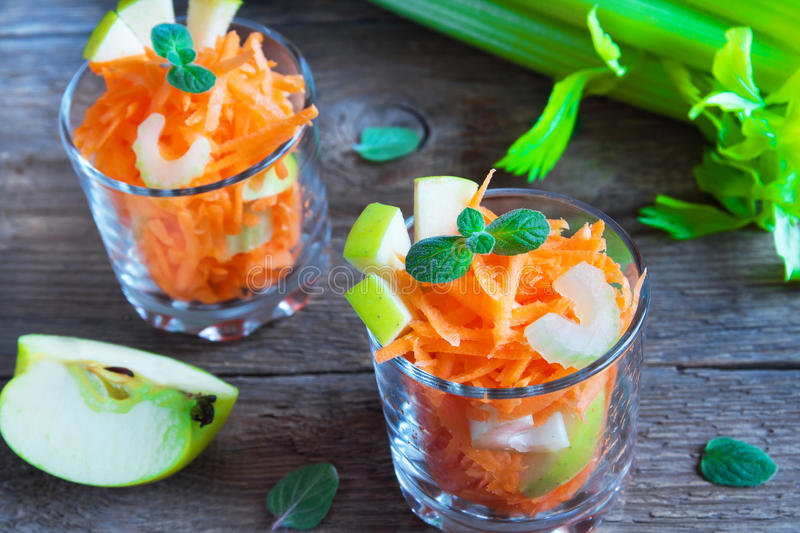 Carrot salad with green apple and celery. In portion glasses royalty free stock photos
