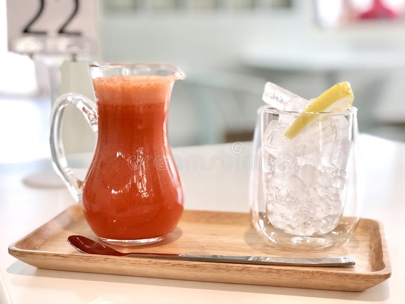 Carrot smoothie in jug drink with ice and lemon, soft drink in beverage and restaurant feeling freshness when drinking, healthy. Carrot smoothie in jug drink stock photo