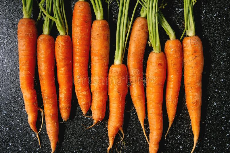 Carrot with tops in row. Young carrot with tops in row over black texture background. Flat lay, space. Cooking concept, food background stock image
