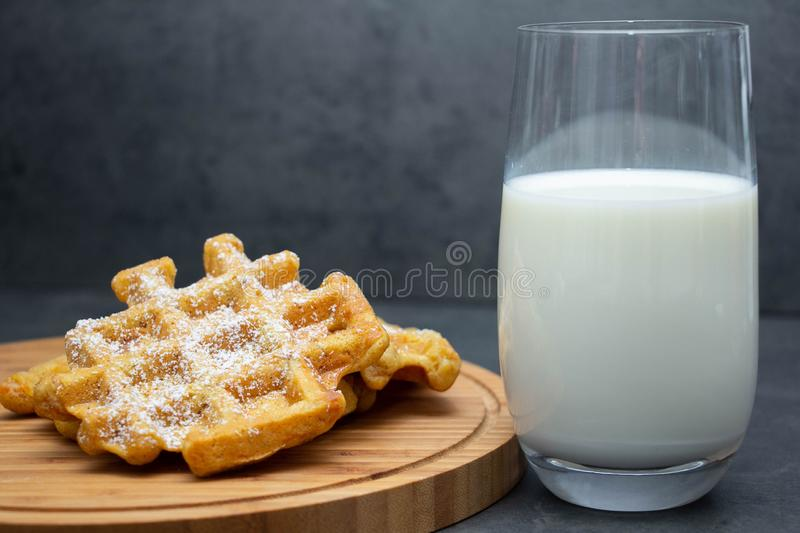 Two homemade carrot waffles on a wooden board, on a wooden round board, sprinkled with powdered sugar with a glass of milk nearby. royalty free stock image
