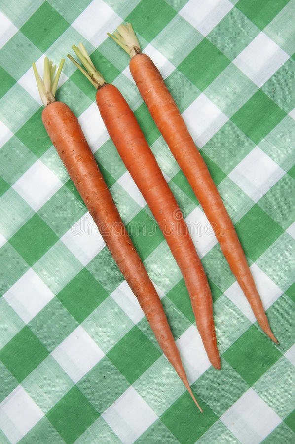 Carrots on Green Checkered Cloth. Carrots on a bright green picnic tablecloth stock image