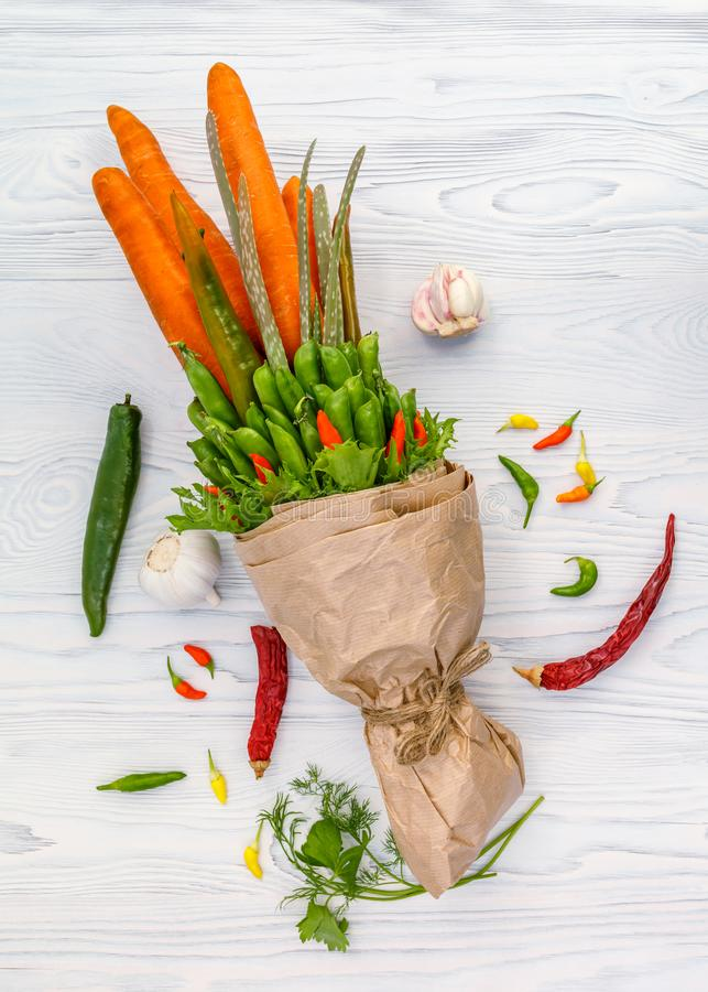 Carrots, peas, peppers and salad leaves in the form of a bouquet lie on a white wooden table.  stock image