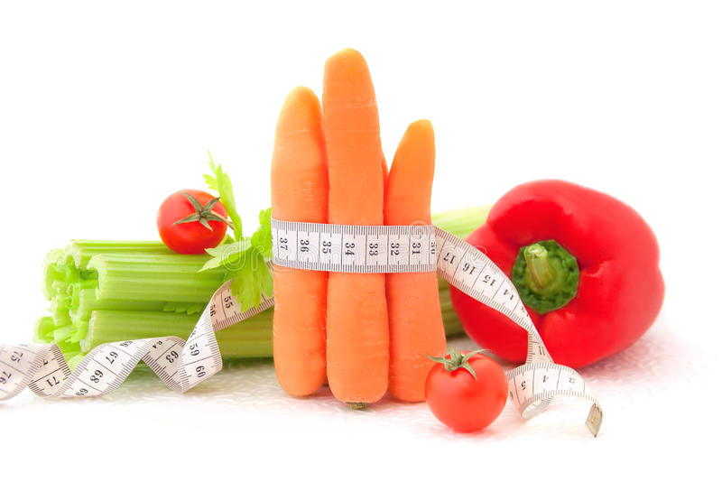 Carrots with tape measure and vegetables royalty free stock photography