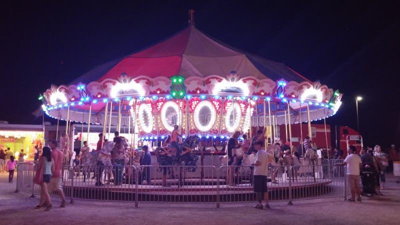 Carrousel bij nacht met rond mensen royalty-vrije stock foto's