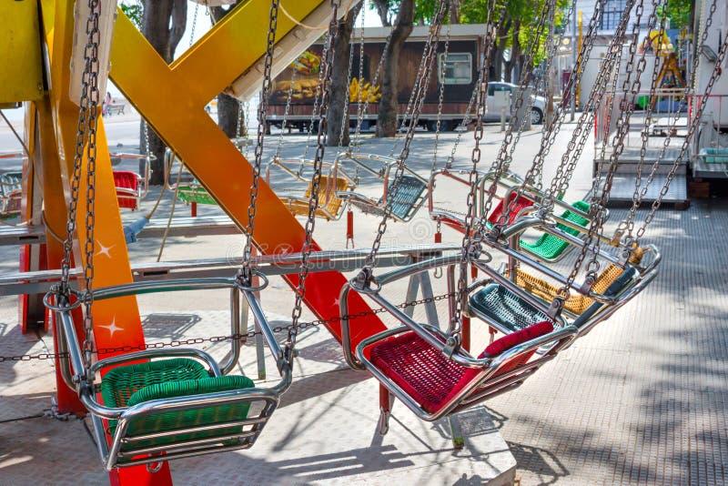 Carrousel vide de siège d'enfant sur des chaînes dans le jour d'été image stock