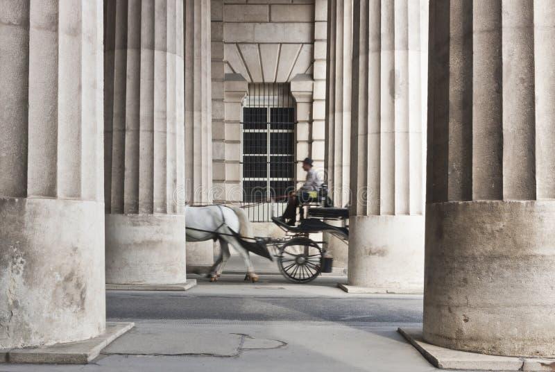 Carrozza a cavalli che passa attraverso il collonnade immagini stock libere da diritti