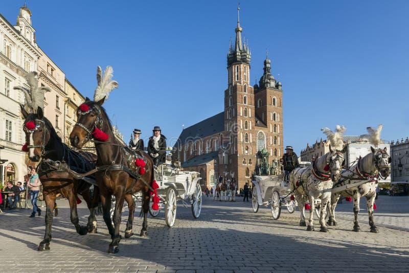 Carrozza a cavalli sul quadrato di Città Vecchia a Cracovia fotografie stock