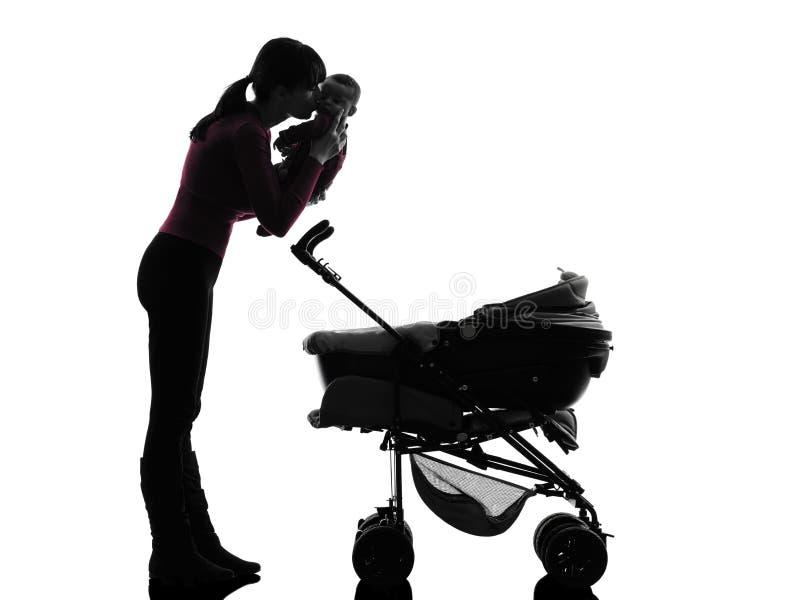 Carrozzine della donna che tengono baciare la siluetta del bambino fotografia stock libera da diritti