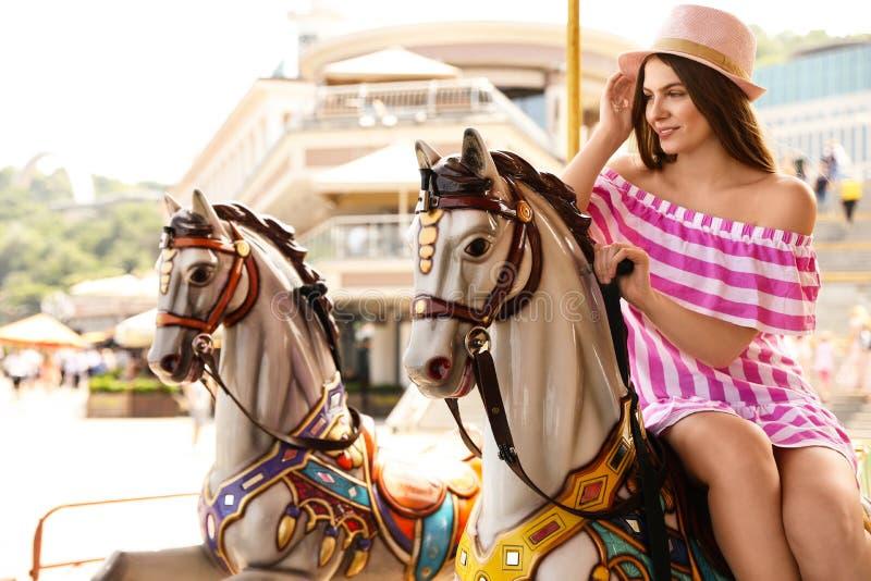 Carrusel bonito joven del montar a caballo de la mujer fotos de archivo libres de regalías