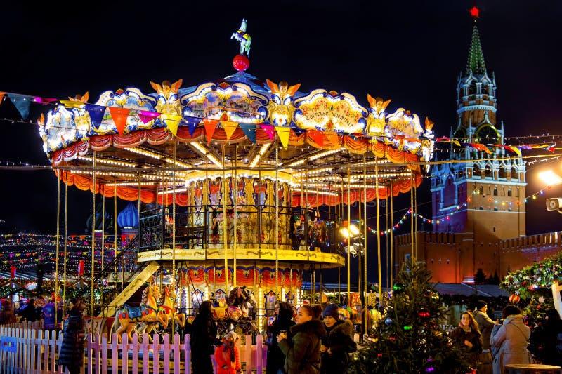 Carrusel colorido antes de la Navidad en el cuadrado rojo del Kremlin Fabuloso, iluminación de la noche, gente que camina foto de archivo