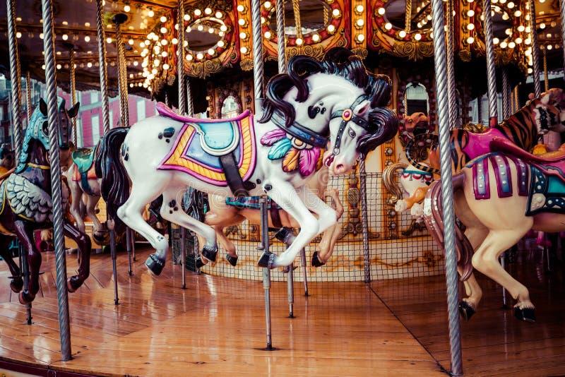 Carrusel francés viejo en un parque del día de fiesta Tres caballos y aeroplanos en un carrusel tradicional del vintage del parqu foto de archivo
