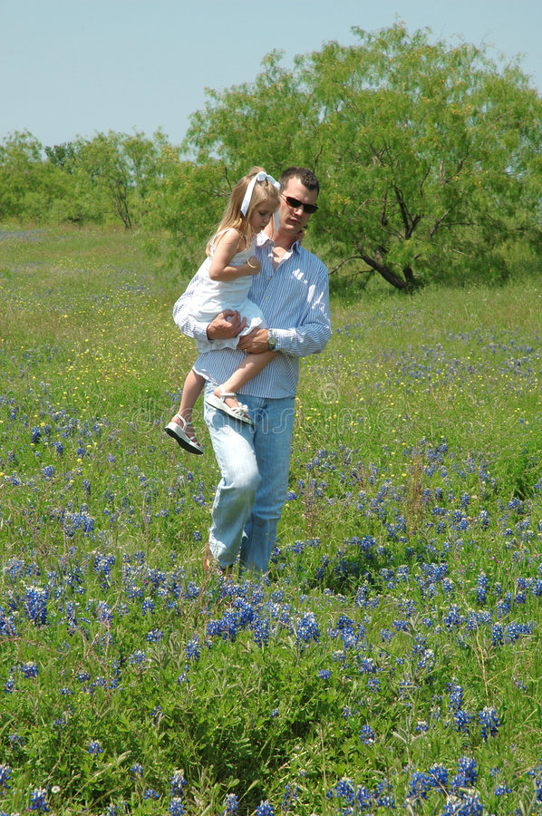 Carry. A father walks threw a field of blue bonnet flowers with his daughter against a blue sky stock image