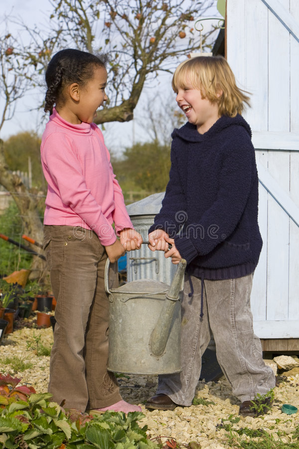 Mixed Race Children Gardening Holding Watering Can stock photo