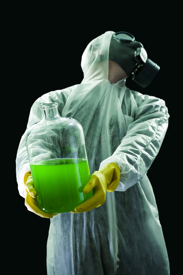 Carrying chemical waste. Man with gas mask and protective suit carrying hazardous chemical waste royalty free stock photo