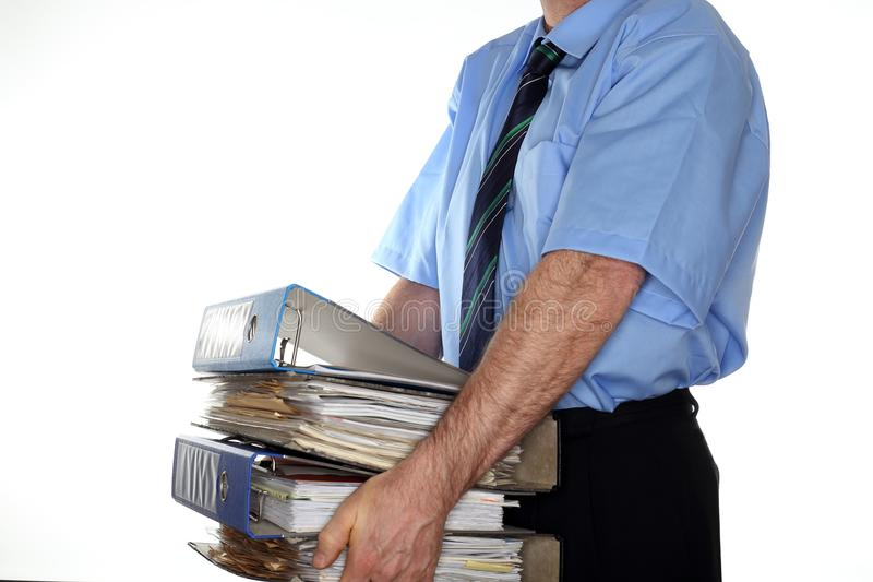 Carrying some heavy file folders. Business man is carrying some heavy file folders stock image