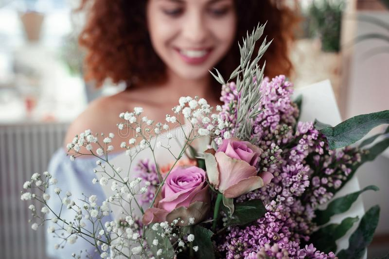 Appealing young woman with ginger hair holding in front of her lilac bouquet royalty free stock image
