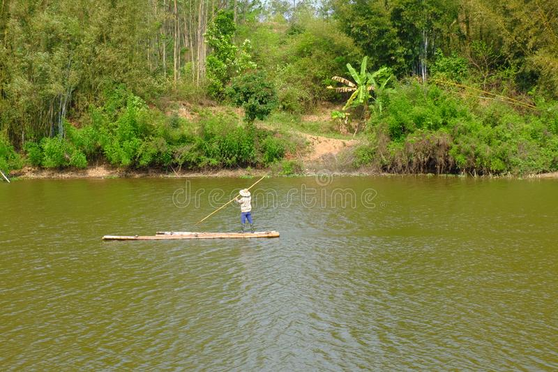 Carrying sugarcane by a bamboo raft. Bamboo raft, tied up with bamboos, are water transport vehicles with mountain streams and water villages. The bamboo raft stock photography
