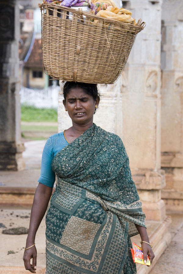 Carrying washing - Chettinad - Tamil Nadu - India. Local woman carrying a basket of washing in the village of Karaikudi in the Chettinad area of the Tamil Nadu stock images
