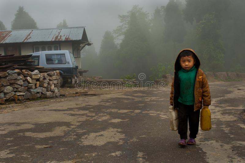Carrying Water. A child boy is carrying jar cans of drinking water in both hands for his home in a misty and rainy morning at nearby villages of Lava, India royalty free stock image