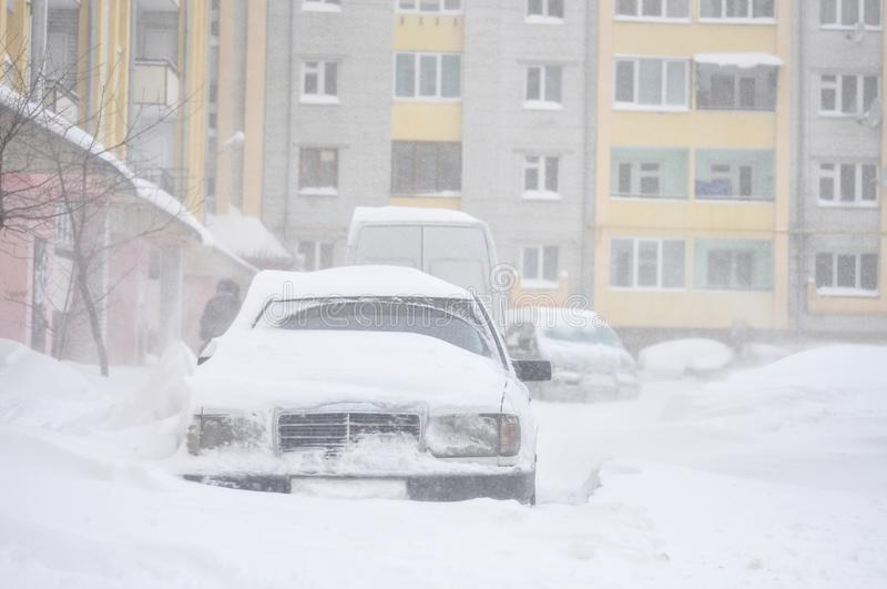 Cars blocked by snow, snow-paralysis of traffic, snow covered street, blizzard, front view, winter weather, work for utility compa stock photography