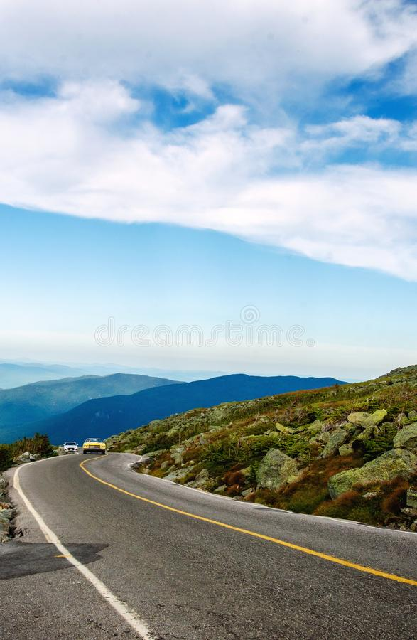 Cars climbing the road to Mount Washington New Hampshire. Cars climbing the steep curved road to the top of Mount Washington, New Hampshire, USA on a summer day stock photography
