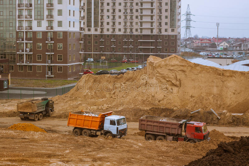 Cars on construction yard buildings background. Process of building,tower cranes brick and concrete buildings stock photos