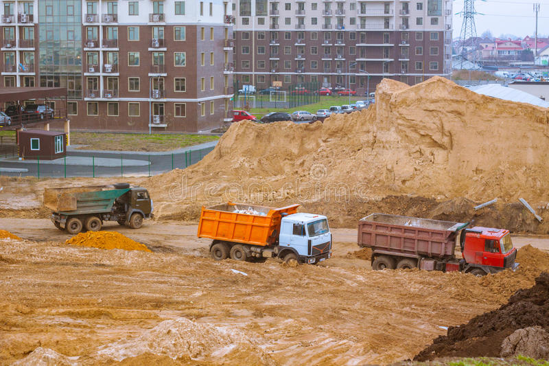 Cars on construction yard buildings background. Process of building,tower cranes brick and concrete buildings royalty free stock photo