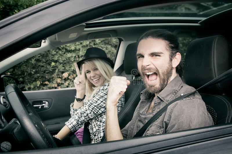 Cars - cool hipster couple driving in new car screaming happy, looking at camera royalty free stock photos
