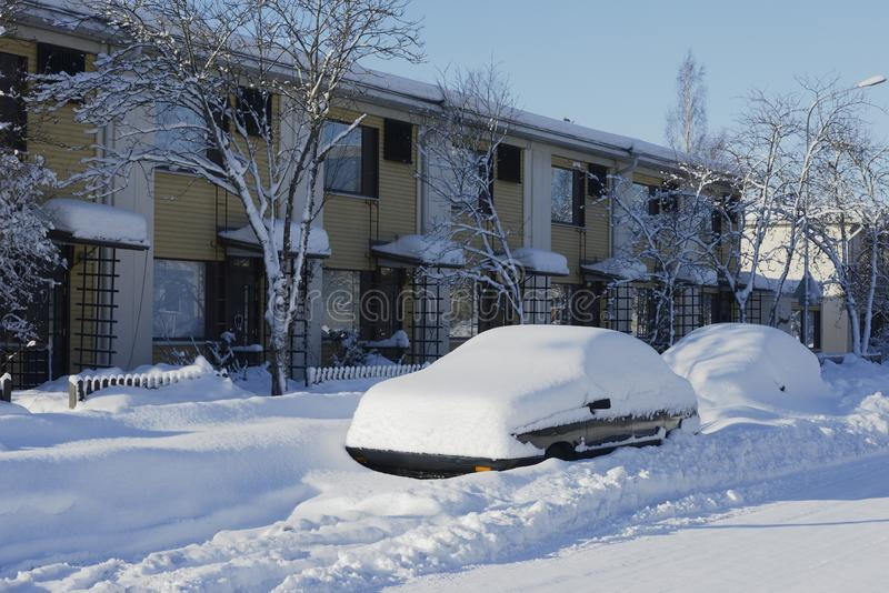 Cars covered in snow near the house stock photo