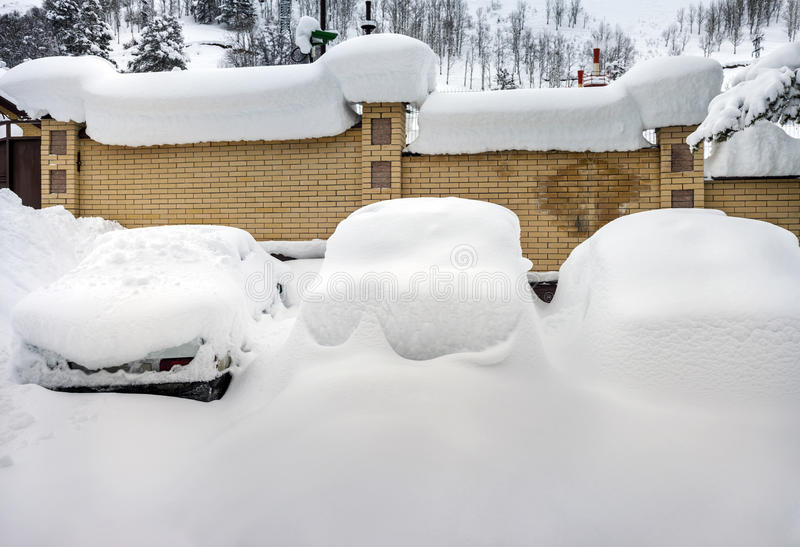 Cars covered with snow. In the parking lot in rural mountain area stock photos