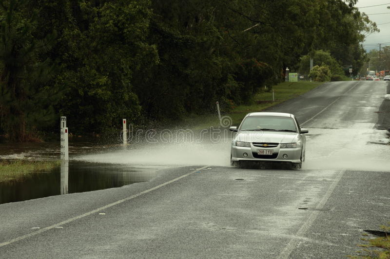 Cars crossing flooded road. BRISBANE, AUSTRALIA - JAN 25 : One year on Brisbane flooding again, cars crossing flooded Burpengary road January 25, 2012 in royalty free stock photo