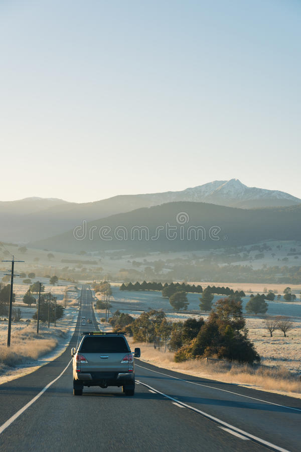 Country highway with cars leading towards mountains at sunrise. Cars driving down a country highway in the early morning as the sun rises casting a warm glow royalty free stock images