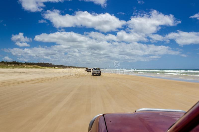 Cars driving on the main transportation highway on Fraser Island - wide wet sand beach coast facing Pacific ocean - long 75 miles stock images