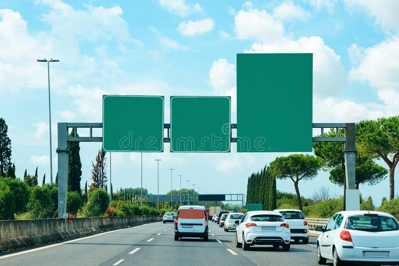Cars and empty green traffic signs on the road royalty free stock image