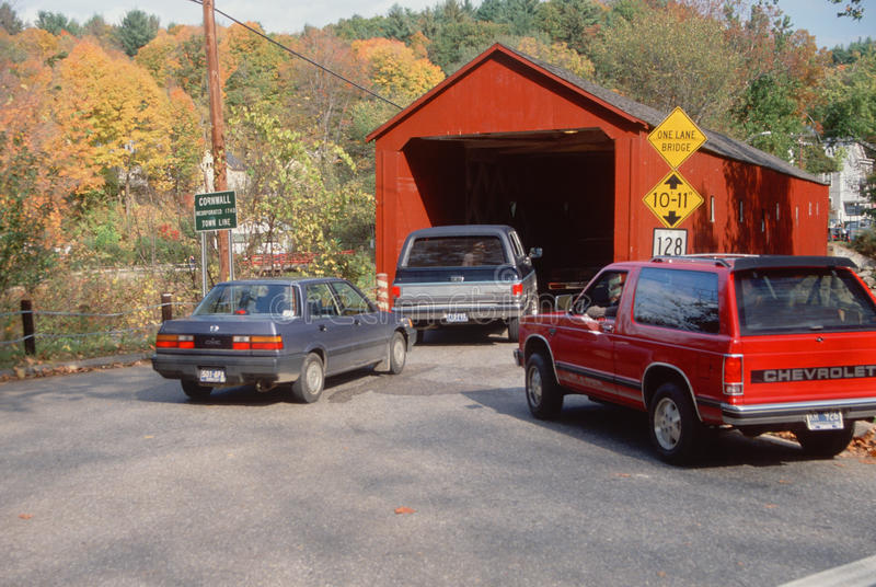 Cars entering covered bridge stock photography