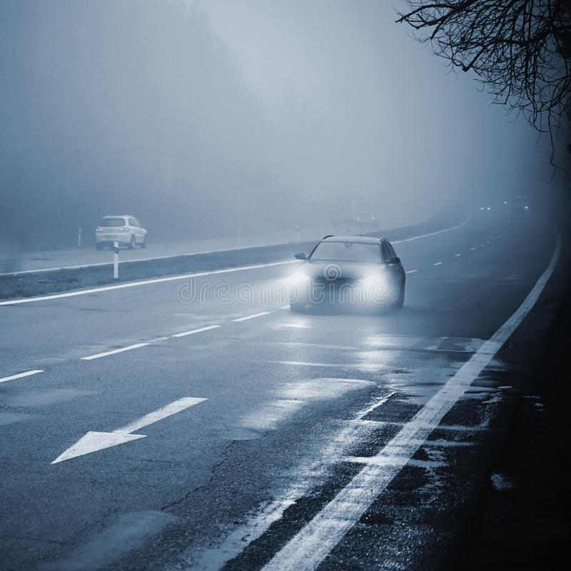 Cars in the fog. Bad winter weather and dangerous automobile traffic on the road. Light vehicles in foggy day.  stock images