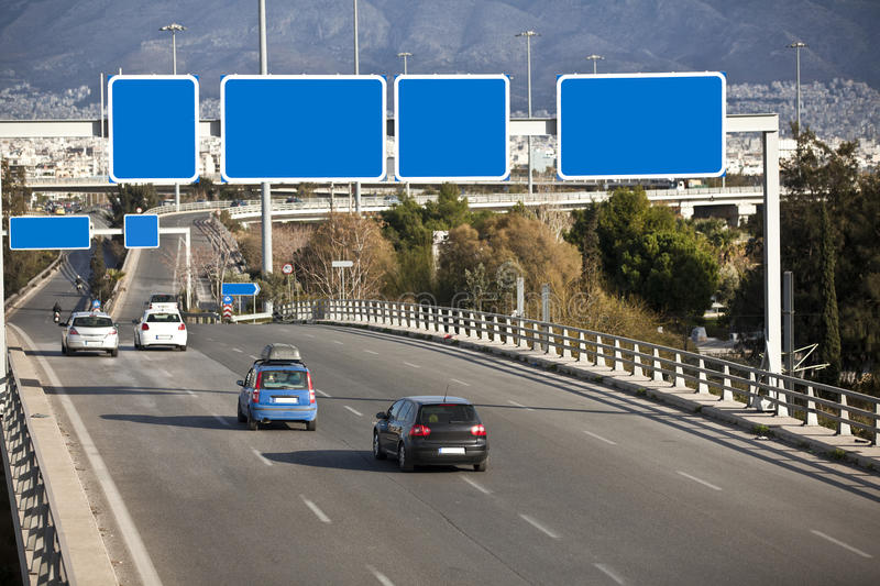 Cars on highway. With blank directional road signs stock image