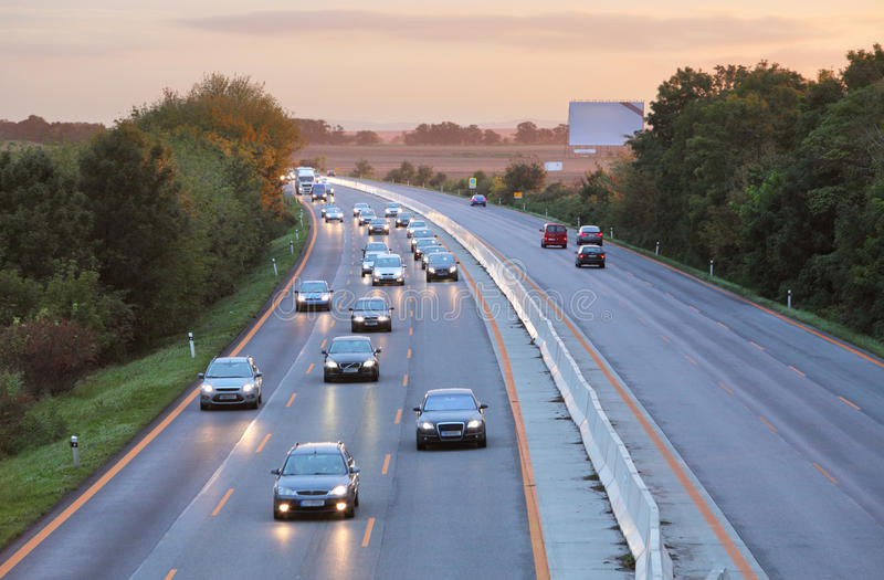 Cars on highway road at sunset stock photo